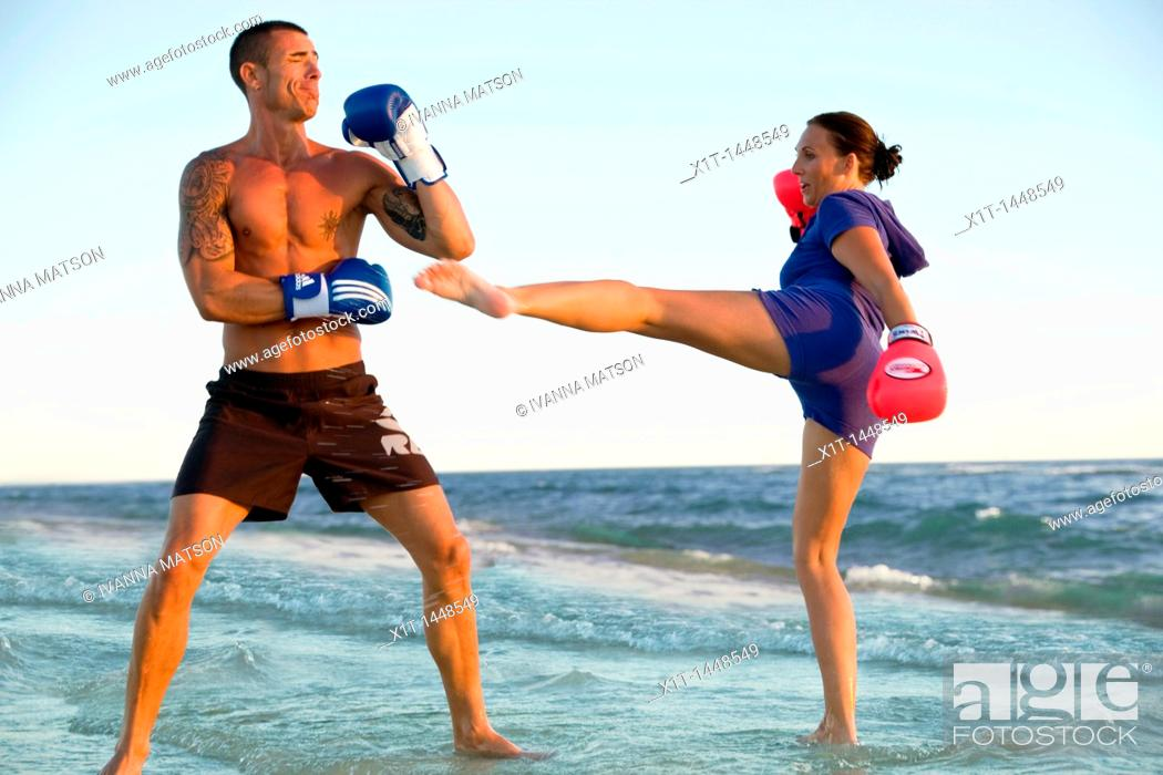 Stock Photo: Couple kickboxing on the beach.