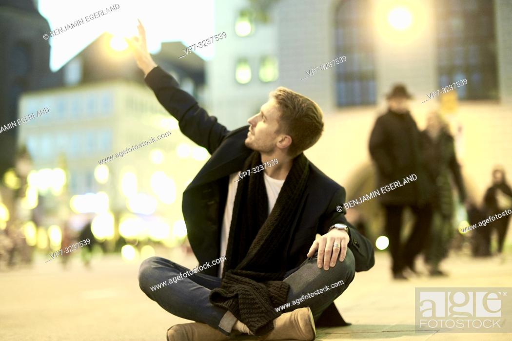 Stock Photo: man sitting on ground at street at night, stretching arm to touch light, in city Munich, Germany.