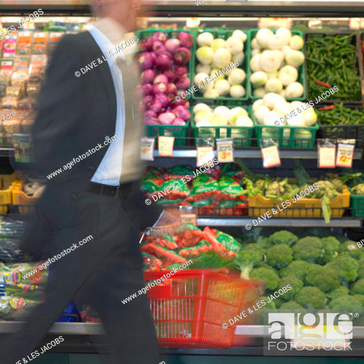 Stock Photo: Blurry view of man walking by produce in supermarket, Perth, Australia.