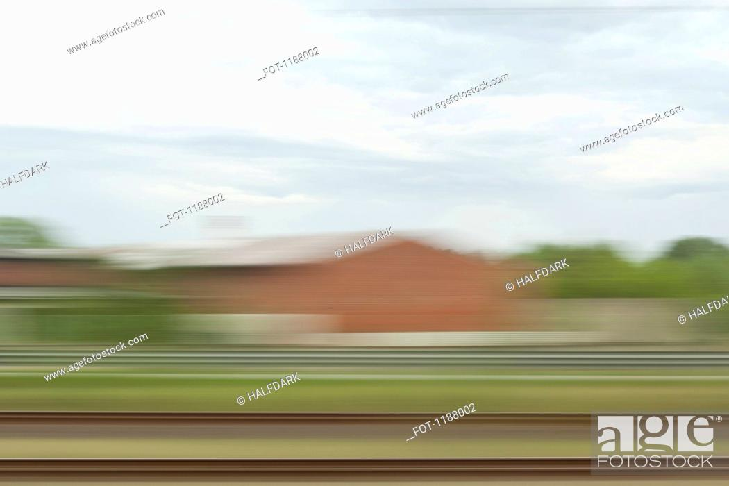 Stock Photo: A landscape with buildings in blurred motion, viewed from moving train.
