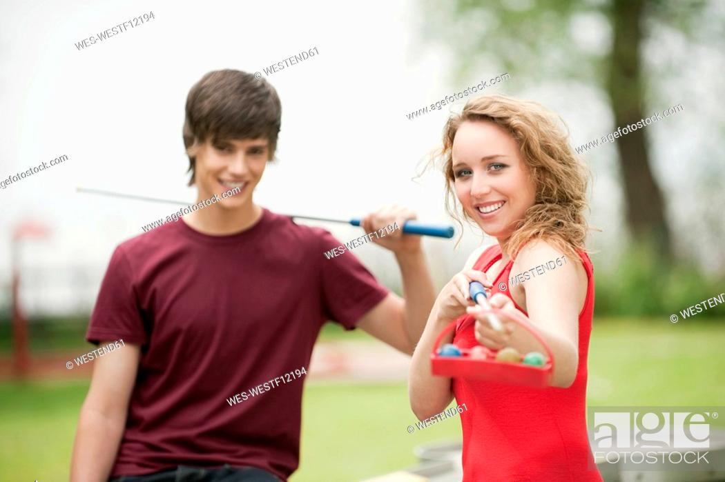 Stock Photo: Germany, Bavaria, Ammersee, Young couple, man holding pool cue, smiling, portrait.