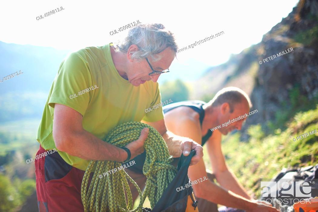 Stock Photo: Rock climbers preparing climbing equipment.