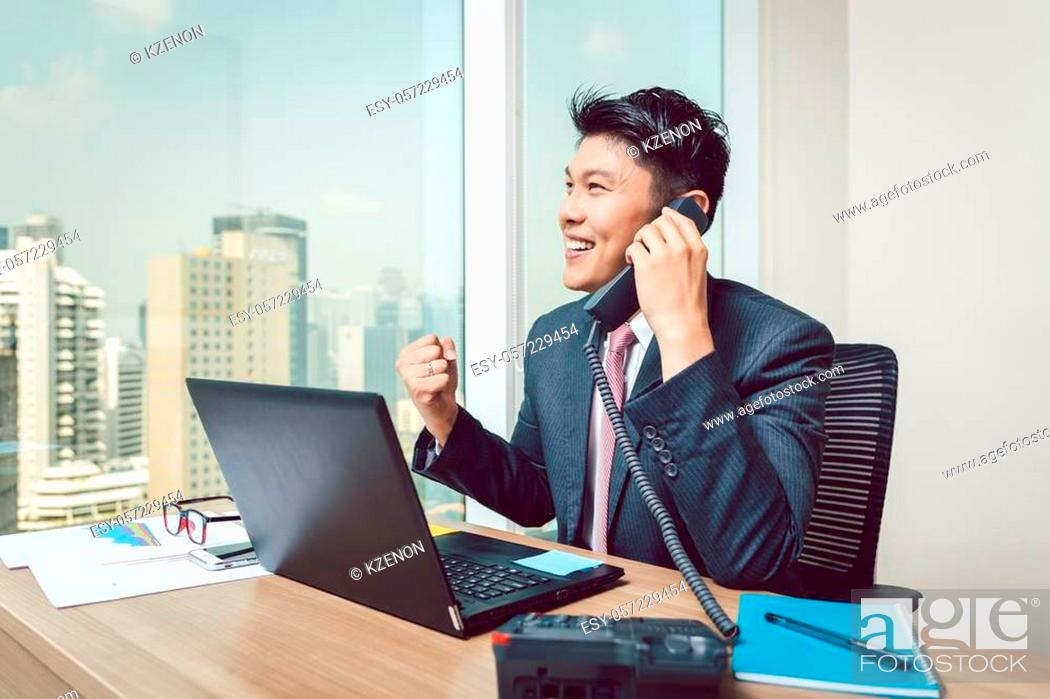 Stock Photo: Portrait of successful smiling young businessman talking on telephone clenching his fist.