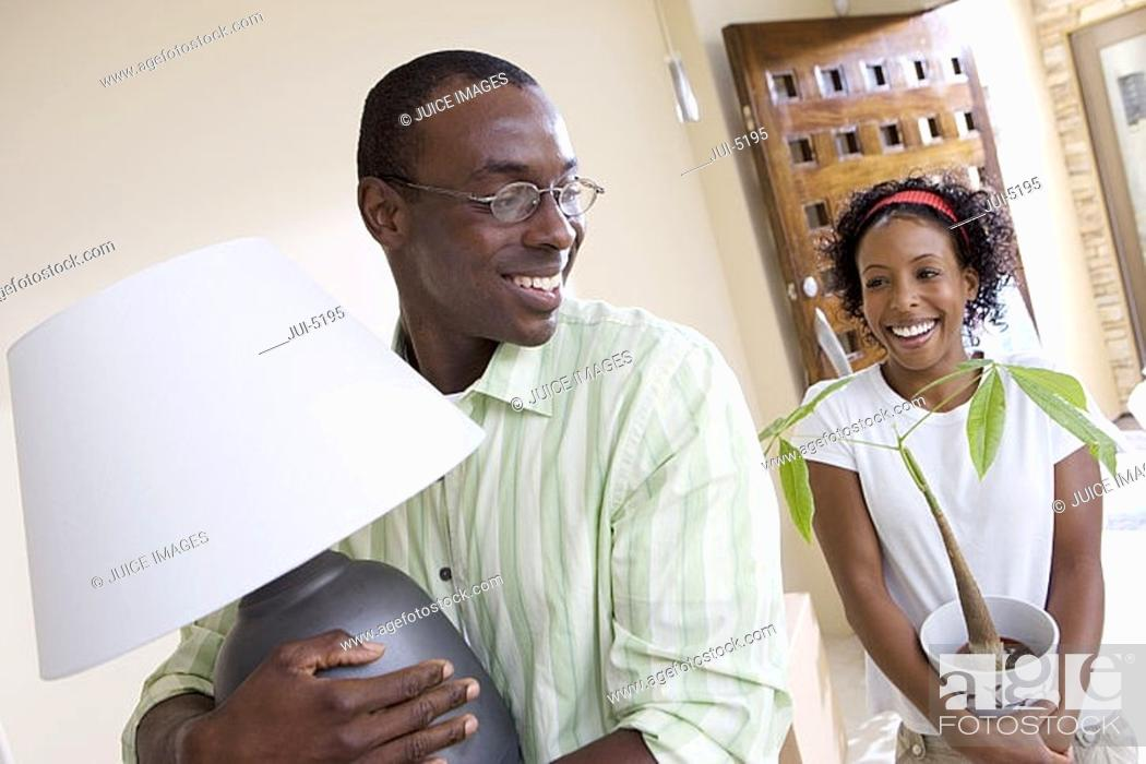 Stock Photo: Couple moving house, woman carrying pot plant, man carrying lamp, smiling tilt.