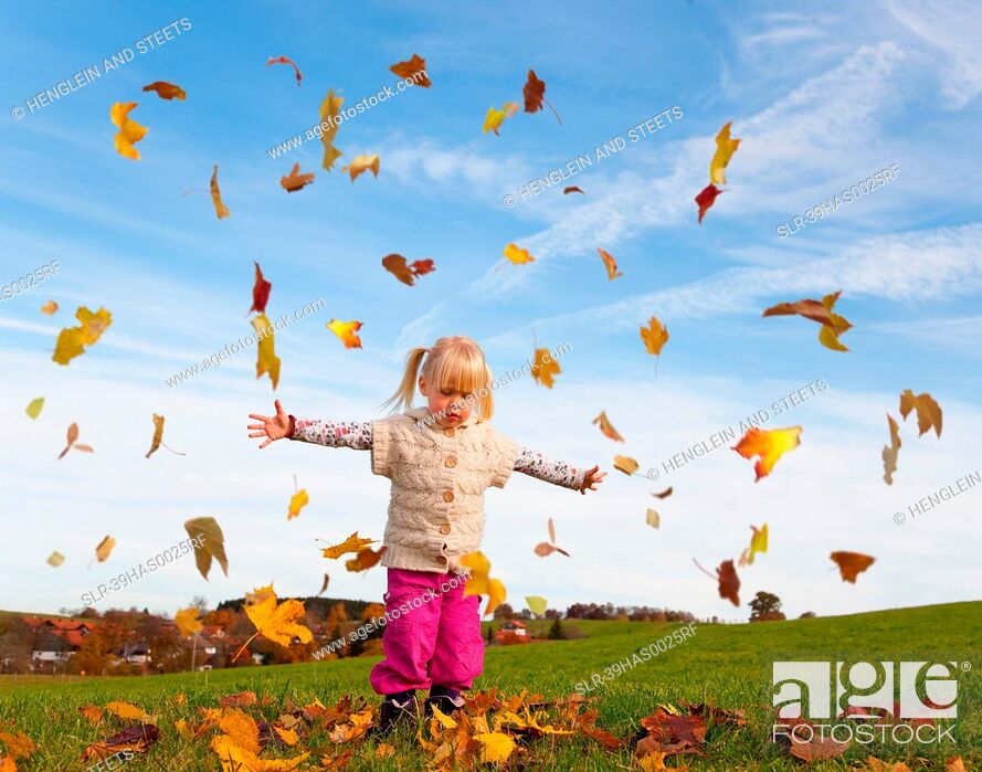 Stock Photo: Girl playing in fall leaves.