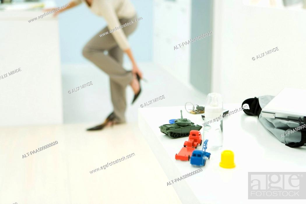 Stock Photo: Professional woman getting dressed, focus on baby bottle and toys in foreground.