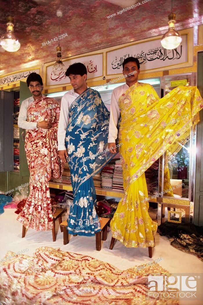 Salesmen modelling saris in a textile and silk sari shop