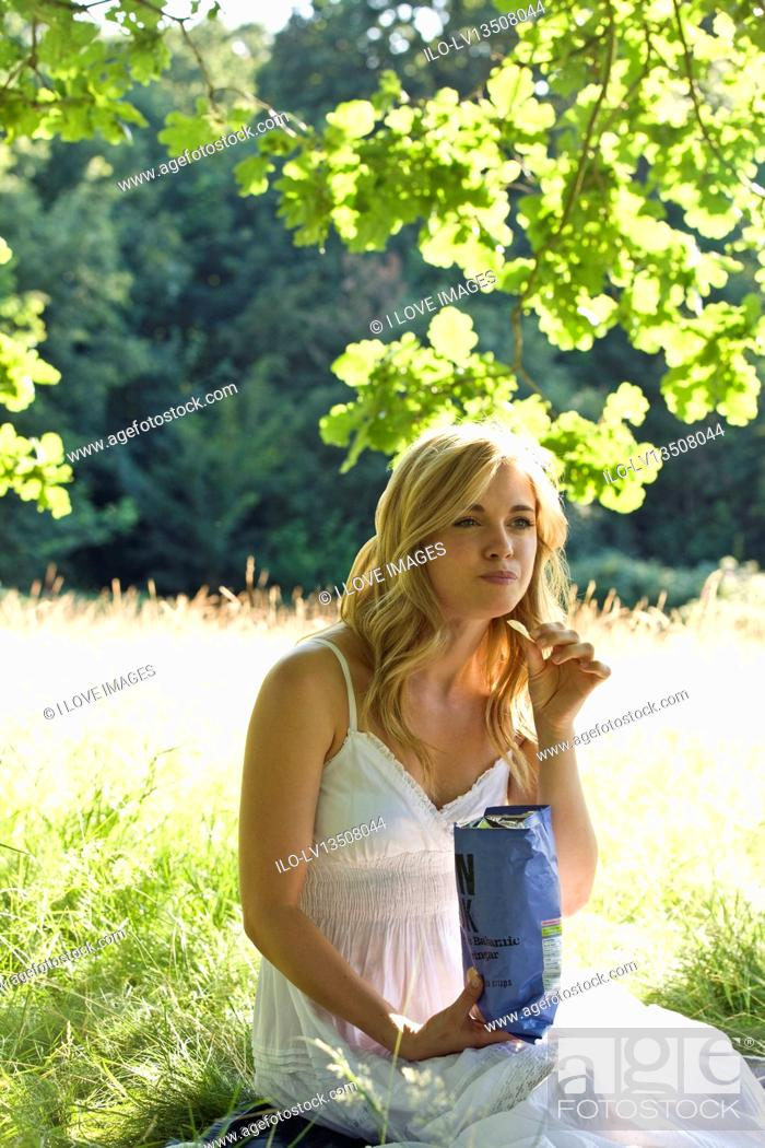 Stock Photo: A young woman sitting on the grass, eating crisps.