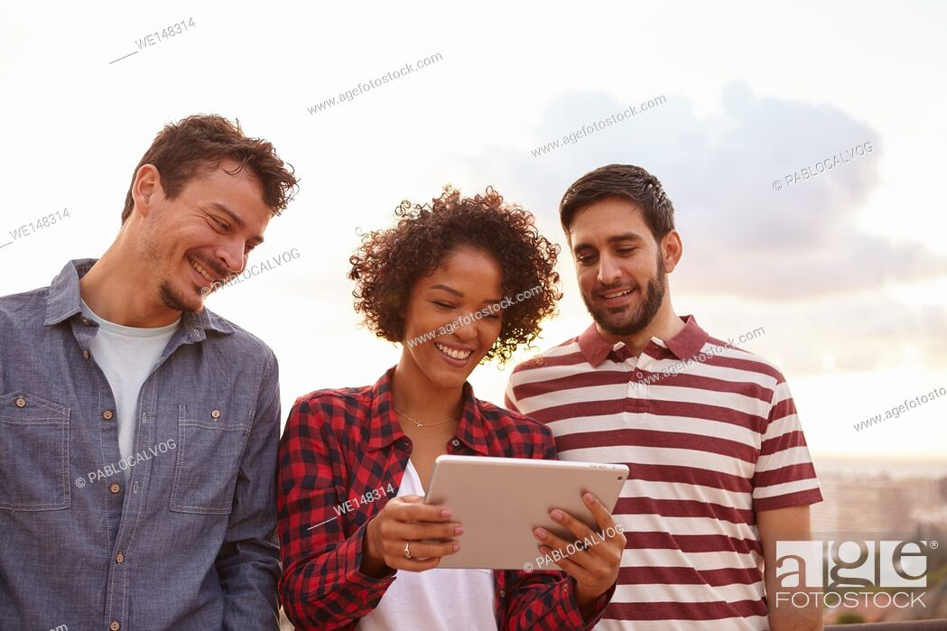 Stock Photo: Three cute friends looking at a tablet with toothy smiles wearing casual clothing on a white background.