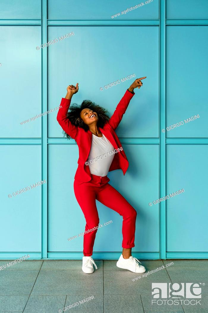 Stock Photo: MId adult woman cheerfully dancing against wall.