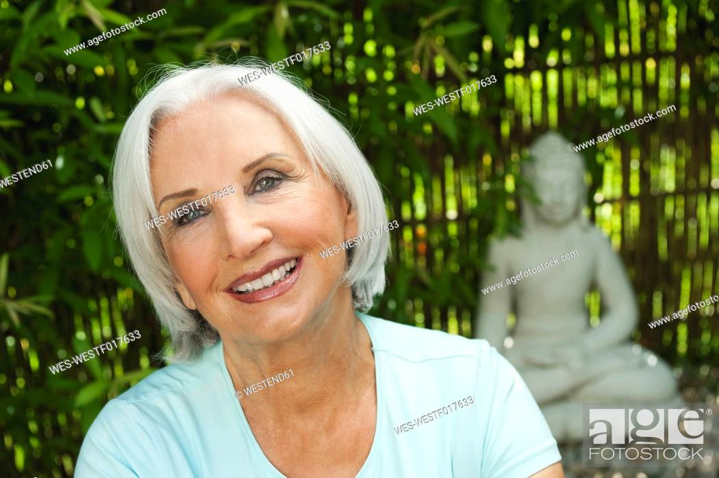 Stock Photo: Germany, Bavaria, Senior woman smiling with buddha statue in background.