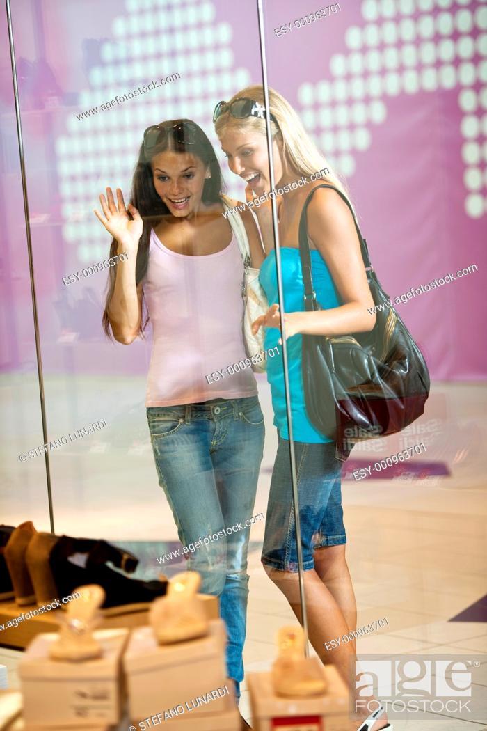 Stock Photo: Young women looking through shop window.