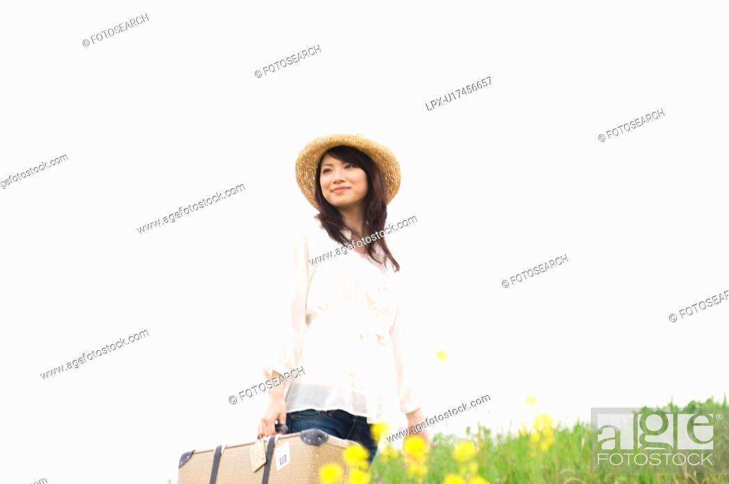 Stock Photo: Woman carrying suitcase walking through a meadow.