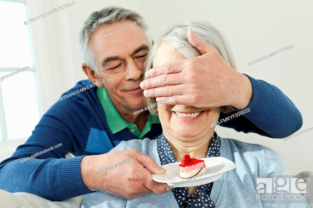 Stock Photo: Germany, Berlin, Man surprising woman with serving cake.