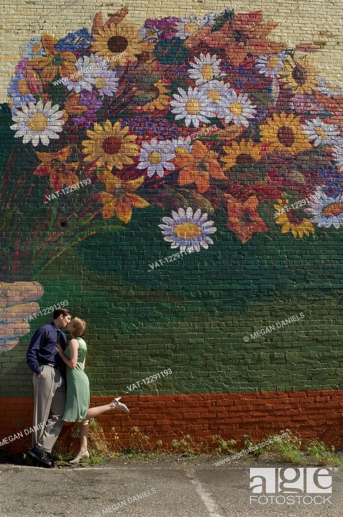 Imagen: A couple kisses as they lean against a wall with a large mural of a colourful bouquet of flowers painted on the wall; Raleigh, North Carolina.