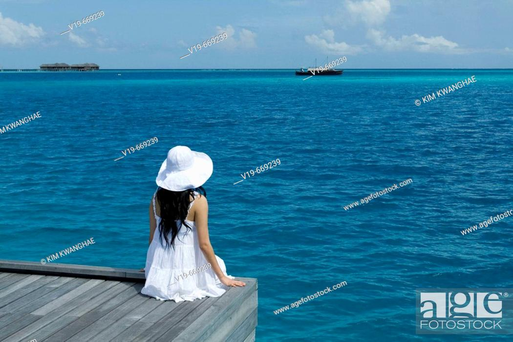 Stock Photo: Womon Sitting on Ocean, Maldives.