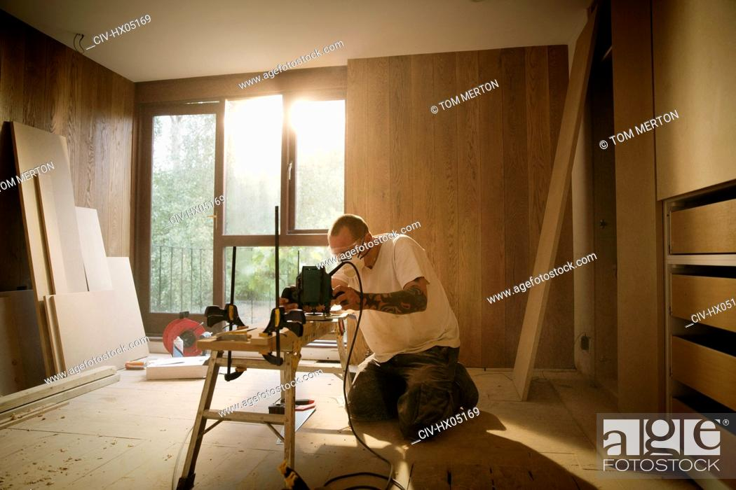Stock Photo: Construction worker using electric saw to cut wood in house.