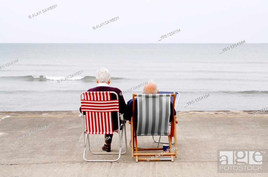 Stock Photo: Elderly couple on deckchairs at the coast  Whitby, North Yorkshire, England.
