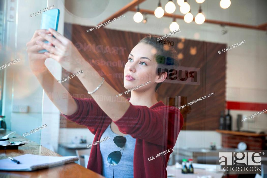 Stock Photo: Young woman sitting in cafe, taking selfie, using smartphone.