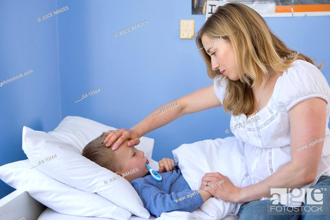 Stock Photo: Mother taking son's 4-6 temperature, side view.