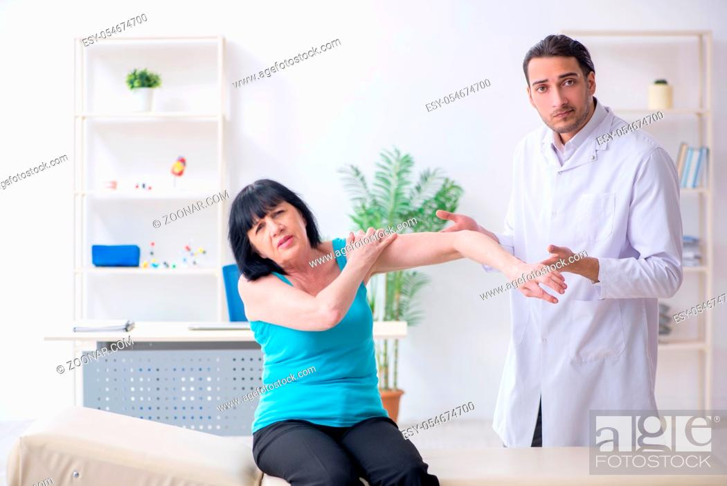 Stock Photo: The young male doctor examining old female patient.