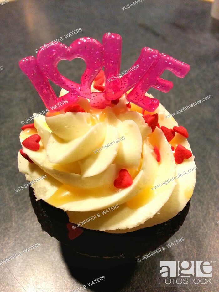 Stock Photo: A cupcake topped with a LOVE decoration.