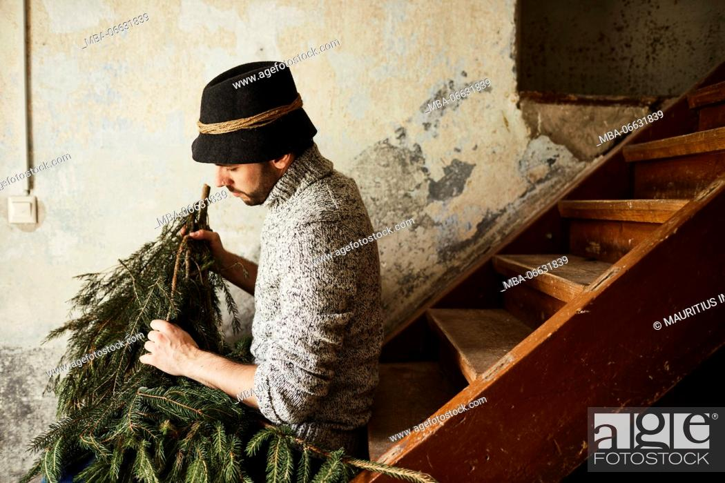 Stock Photo: Man with knitted pullover and hat, twigs of evergreens for decoration, stairs, sit, sitting, half-portrait, side view,.
