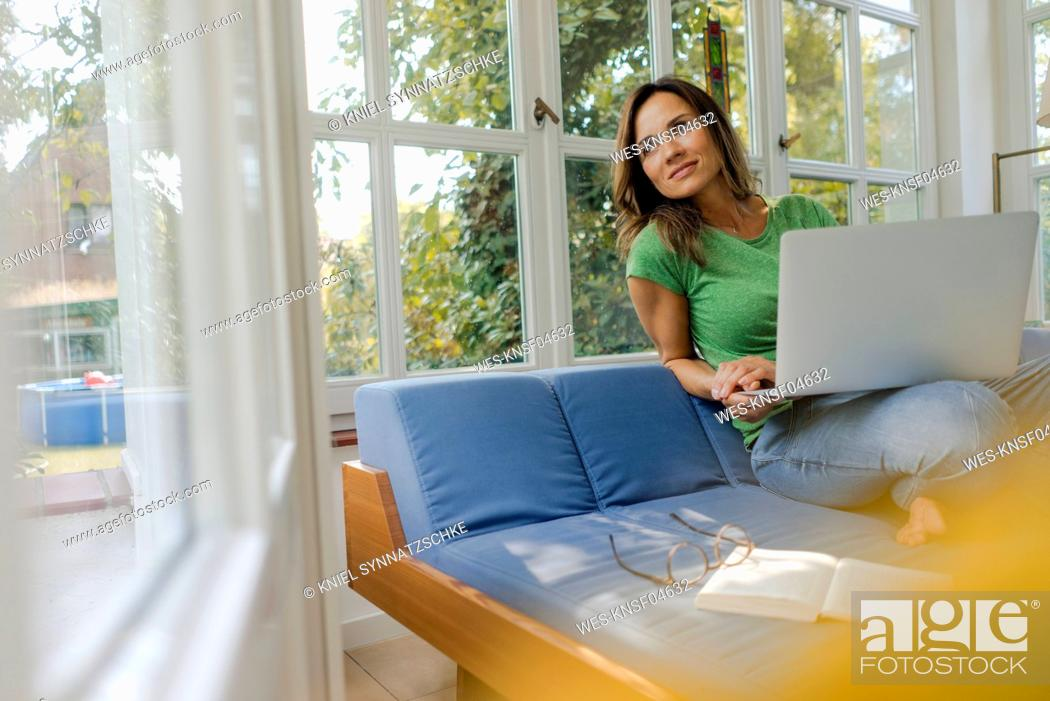 Stock Photo: Smiling mature woman sitting on couch at home with laptop.
