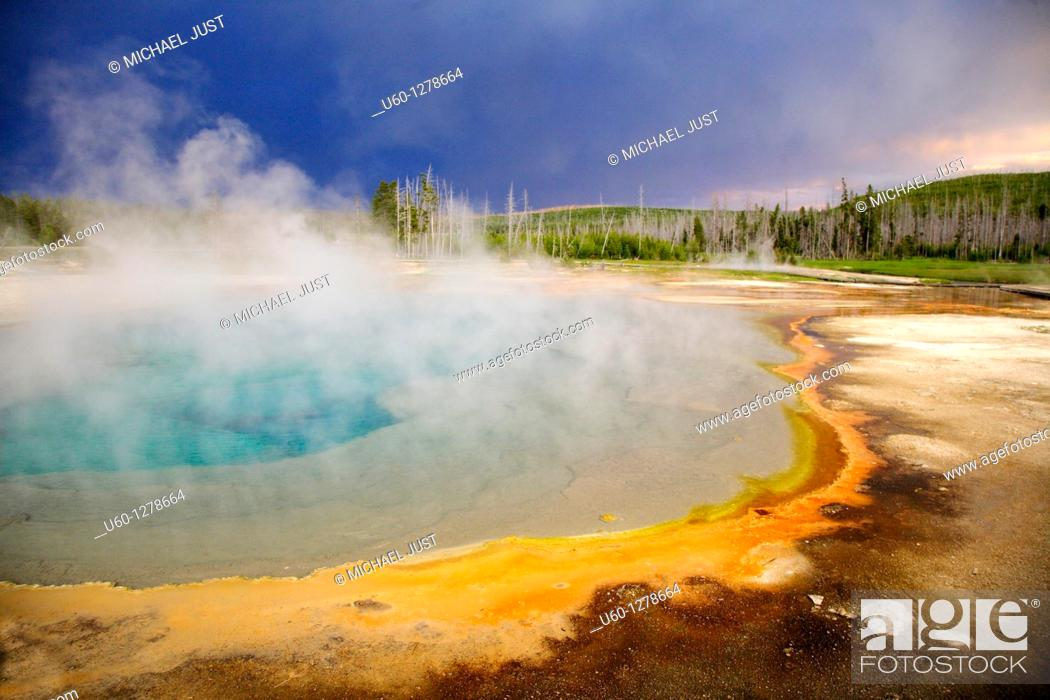 Stock Photo: Dark clouds from a summer thunderstorm pass over black sand geyser basin in Yellowstone national park, wyoming.
