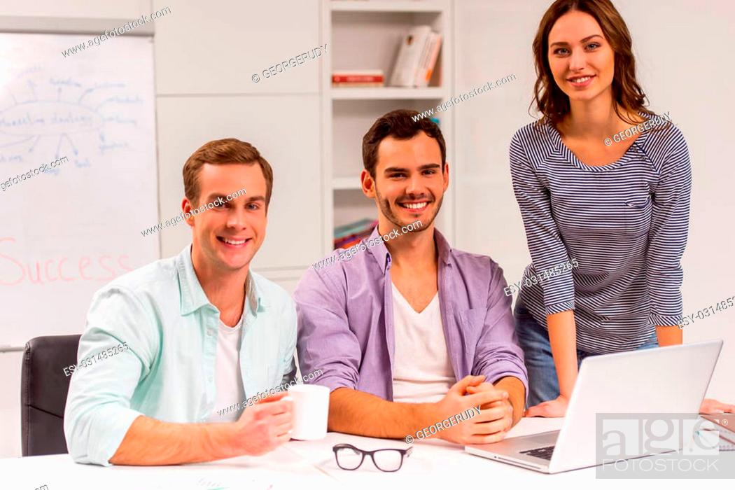Photo de stock: Two young attractive businessmen and one beautiful businesswoman in casual clothes using laptop, looking in camera and smiling while working in office.
