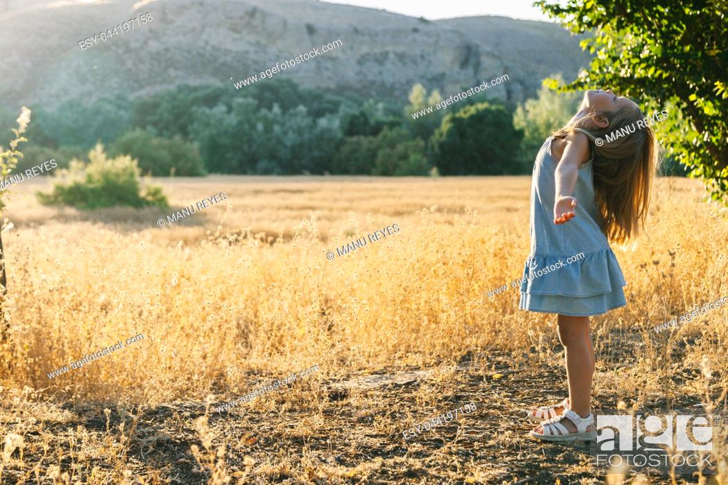 Stock Photo: Young blonde girl playing with sunlight in the fields sunset wearing a dress with hill in the background.