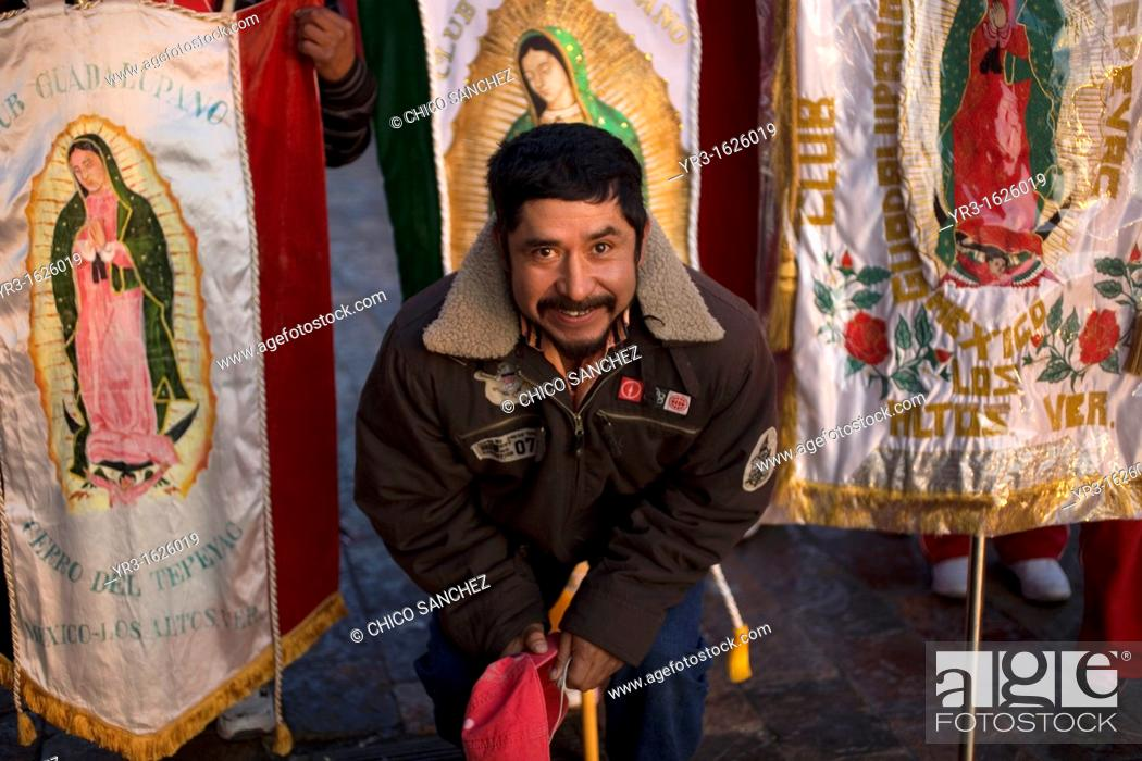 Stock Photo: A pilgrim poses with banners with the image of Our Lady of Guadalupe virgin enter Our Lady of Guadalupe Basilica in Mexico City, December 9.