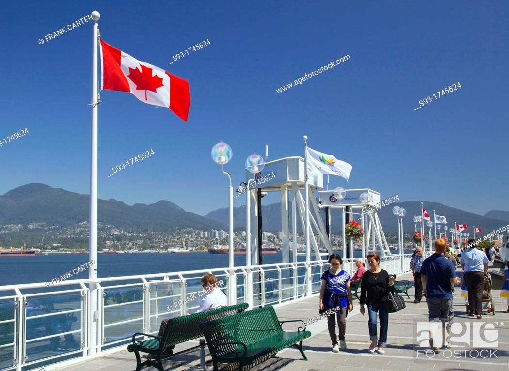 Stock Photo: People walking on the deck beside Canada Place, with Canadian flags in the background.