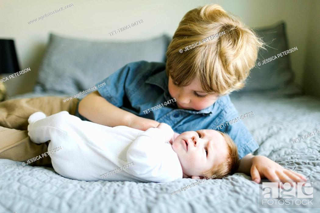Stock Photo: Boy and his baby brother on bed.