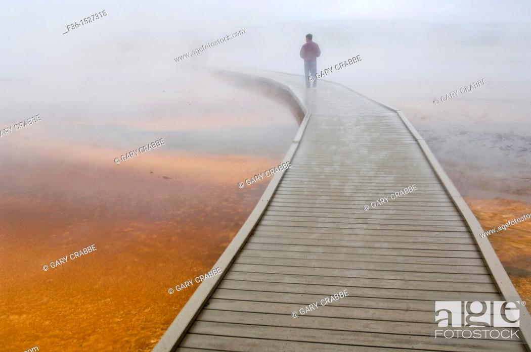 Stock Photo: Tourist on boardwalk in steam over the fragile ground at the Grand Prismatic Spring, Midway Geyser Basin, Yellowstone National Park, Wyoming.