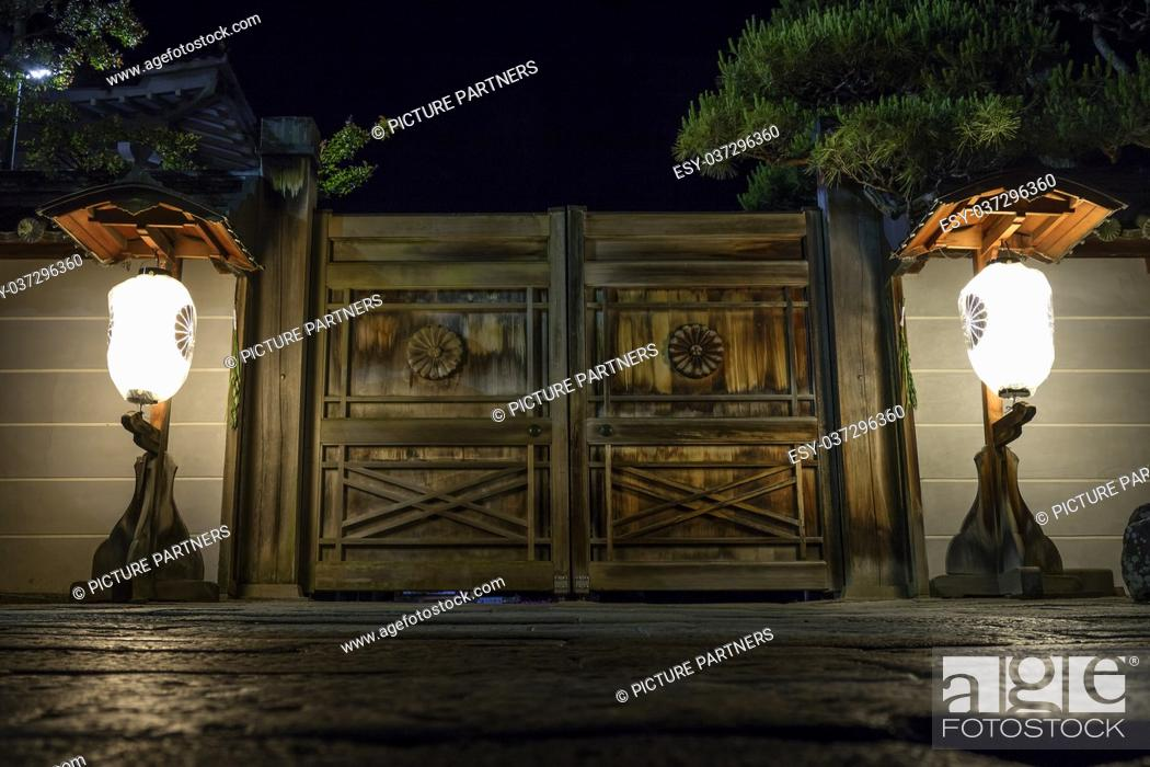Photo de stock: Illuminated lanterns in front of wooden doors to a temple gate on the road to Zenkoji in Nagano at night.