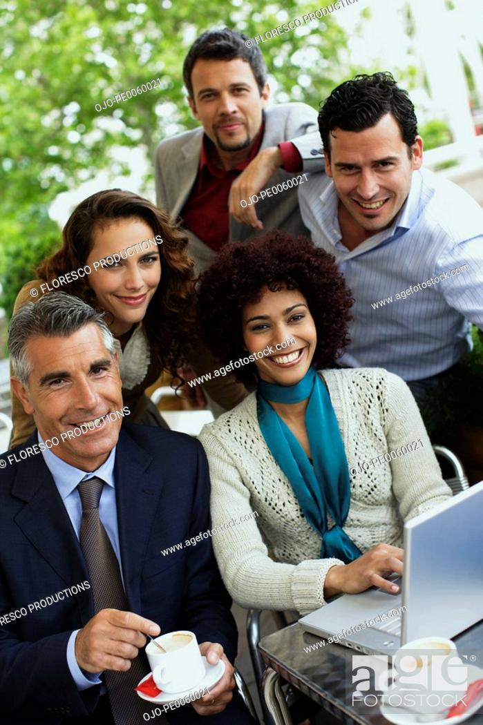 Stock Photo: Five businesspeople on outdoor patio with laptop.