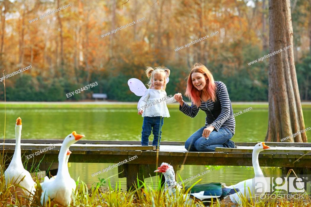 Stock Photo: Kid girl and mother playing with ducks in the park lake.