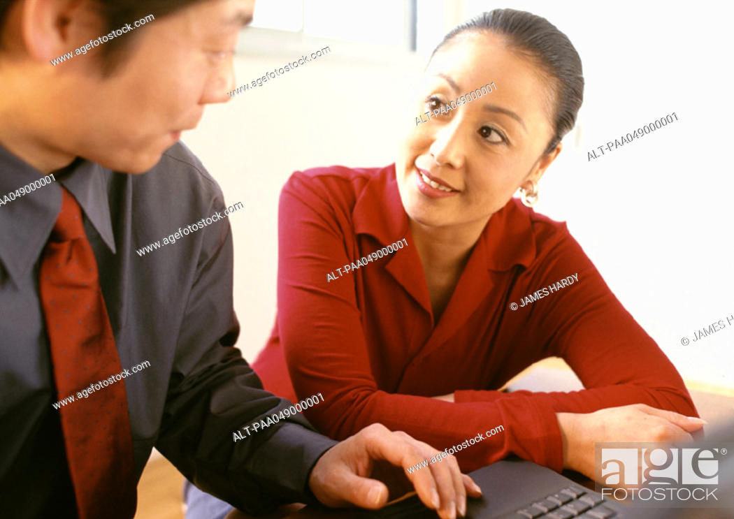 Stock Photo: Man and woman sitting side by side, man's hand on keyboard.