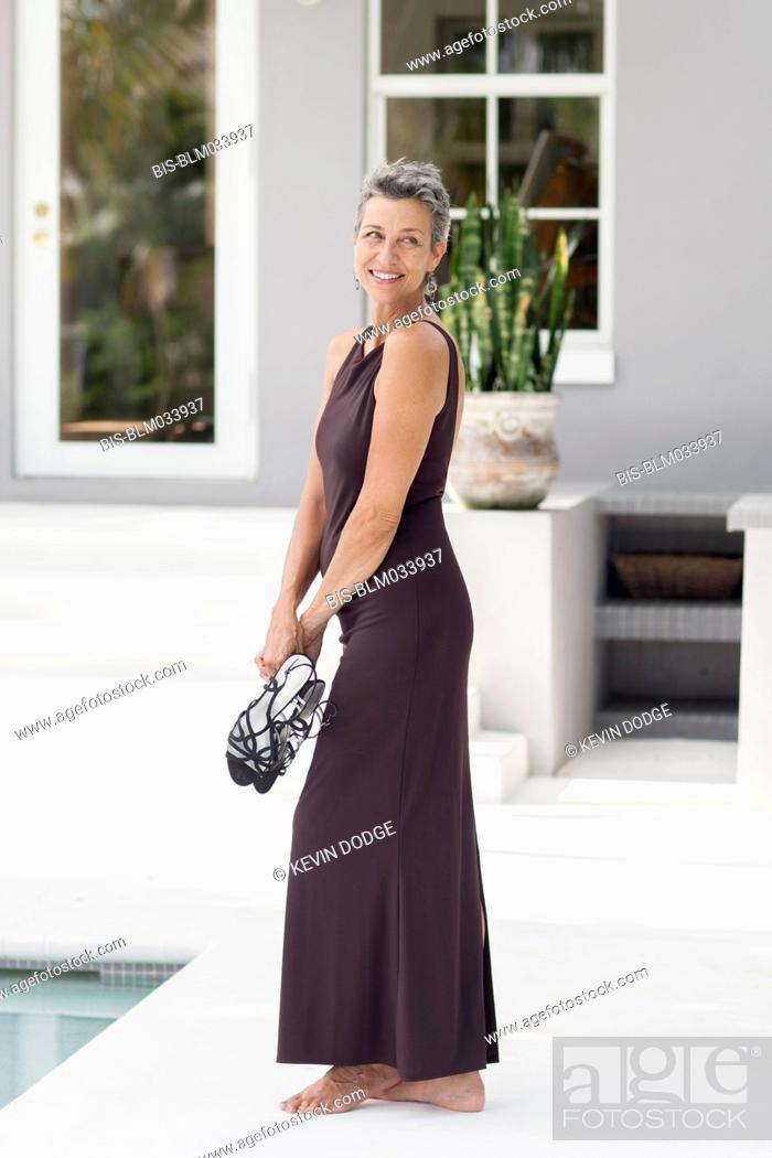 Woman in evening gown carrying shoes by swimming pool, Stock Photo ...