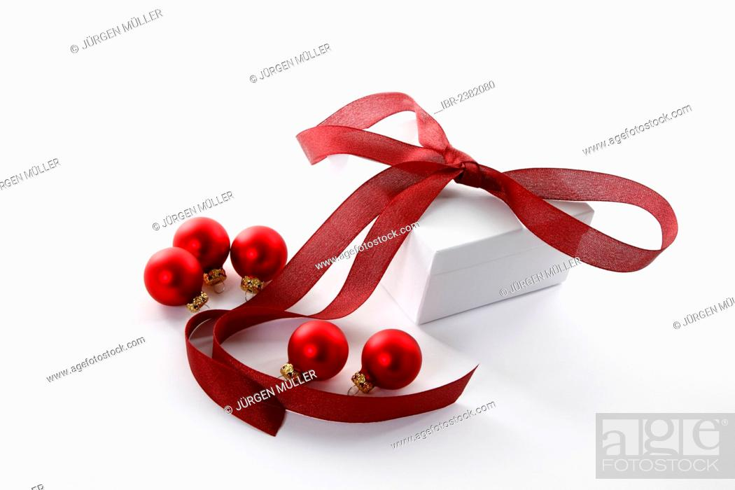 Imagen: Red Christmas baubles and a present with a red ribbon.