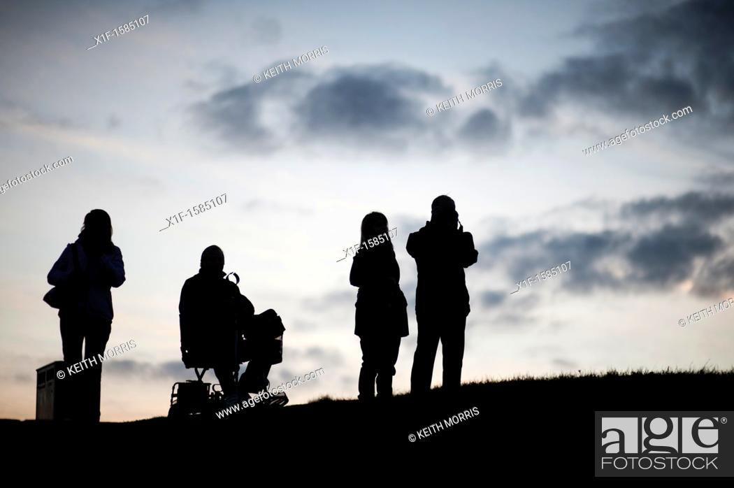 Stock Photo: Four people, one in a wheelchair, silhouetted against the sky, Aberystwyth at dusk, October 2011.