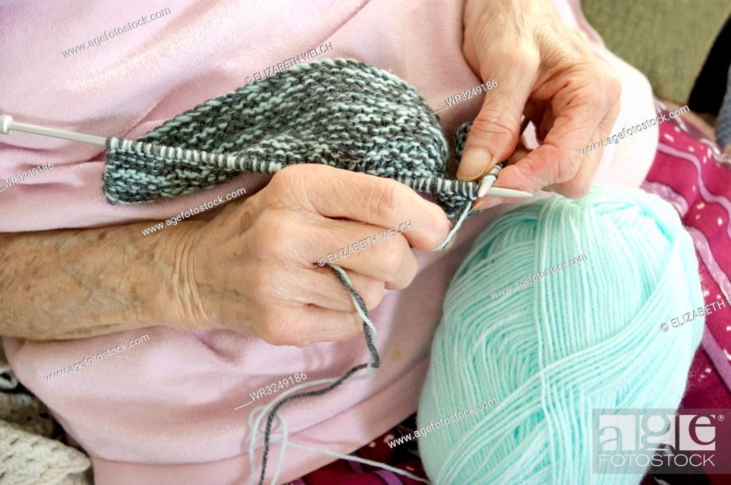 Stock Photo: Elderly woman knitting a garment.