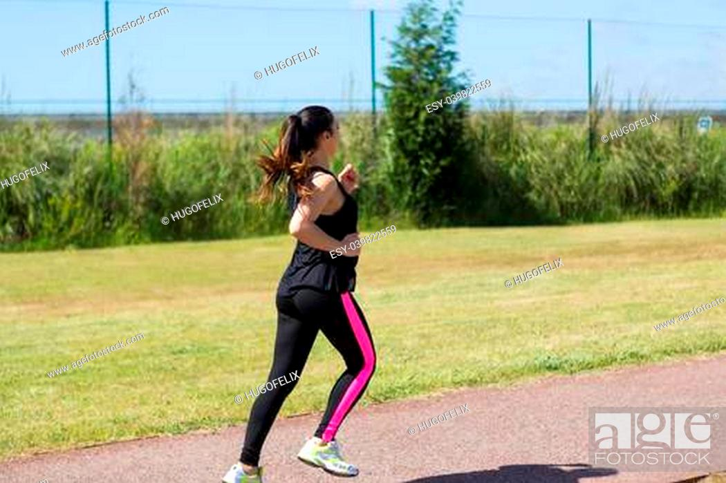 Stock Photo: A beautiful young woman making some exercise at the park - fitness concept.
