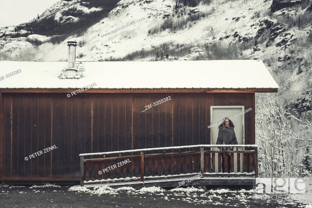 Stock Photo: A young Woman is wrapped in a woolen blanket outside of a simple wooden cabin. Yukon Territory, Canada.