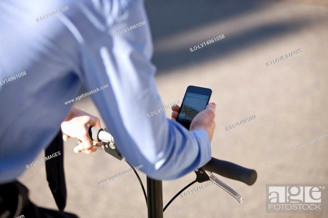 Stock Photo: A businessman on his bicycle, looking at a map on his mobile phone.