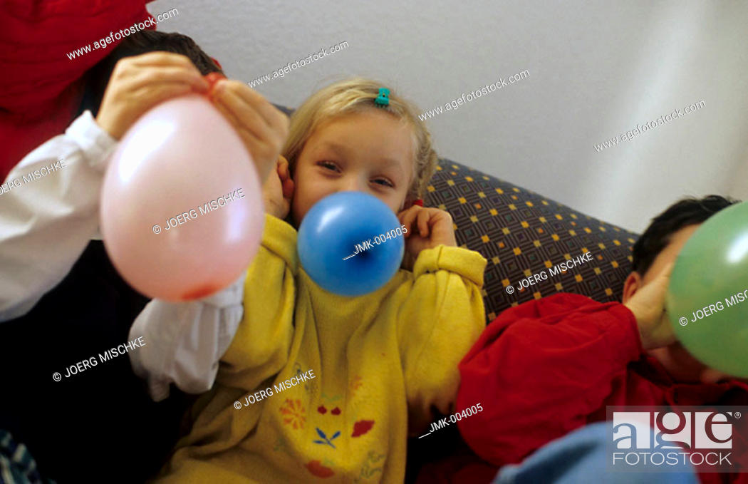 Stock Photo: Three children, boys and a girl, 5-10 years old, sitting on a sofa, inflating balloons.