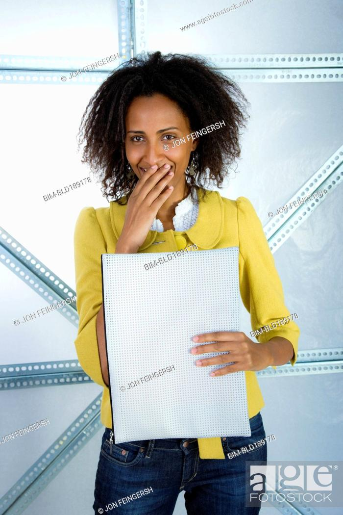 Stock Photo: Surprised Ethiopian businesswoman holding envelope.