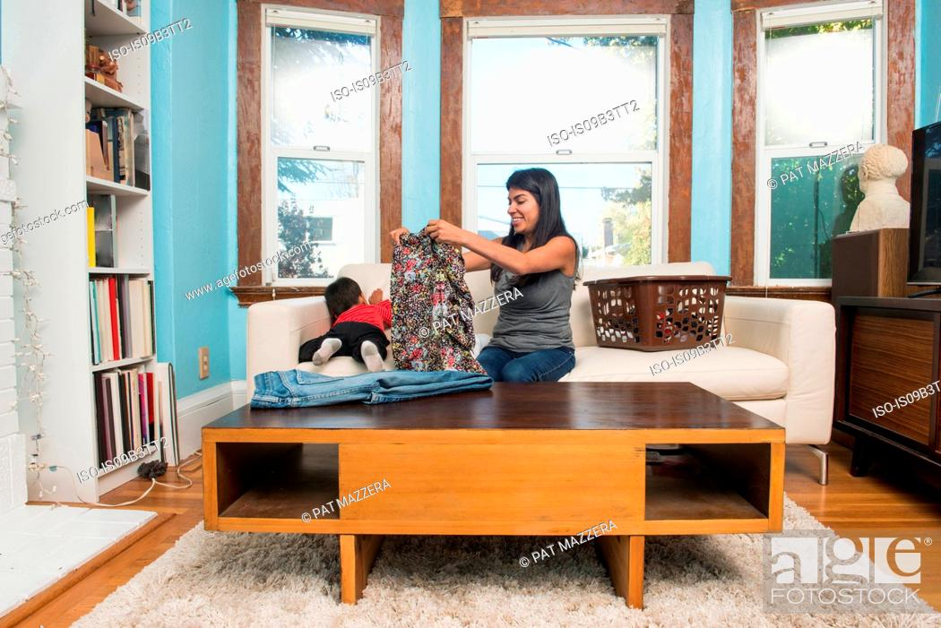 Stock Photo: Male toddler climbing on sofa while mother folding laundry.