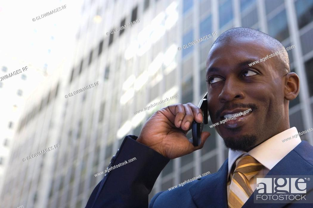Stock Photo: Low angle view of a businessman talking on a mobile phone and smiling.